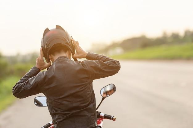Motocyklista jest ubranym skórzaną kurtkę i trzyma hełm na drodze