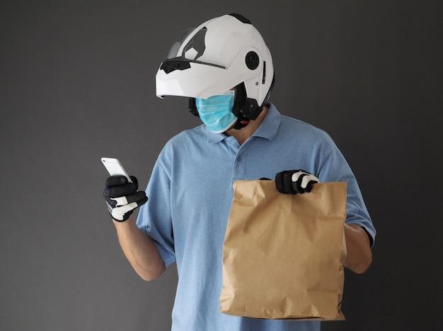 Motocyklista kurier w białym kasku i masce ochronnej trzymający torbę z jedzeniem