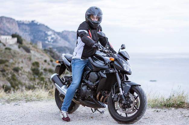 Motocyklista młody człowiek z jego czarny motocykl gotowy do jazdy, przed morzem