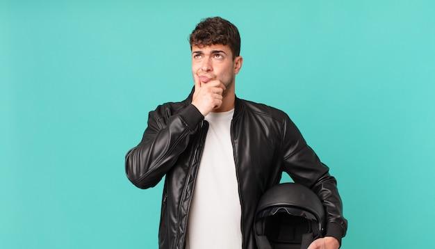 Motocyklista myśli, czuje się zwątpienie i zdezorientowany, z różnymi opcjami, zastanawiając się, którą decyzję podjąć