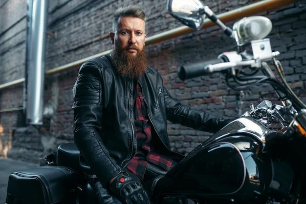 Motocyklista pozuje na klasycznym chopperze, motocyklistą. vintage rowerzysta na motocyklu, styl życia wolności