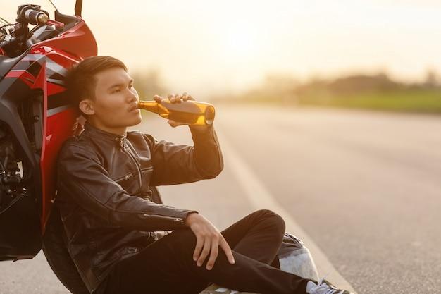 Motocyklista siedzi na drodze obok motocykla i pije piwo