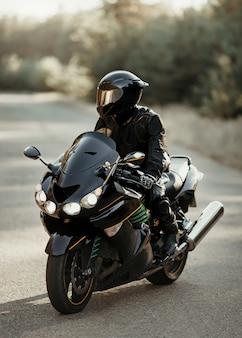 Motocyklista w kasku na motocyklu na wiejskiej drodze. facet prowadzący rower podczas wycieczki. jazda na nowoczesnym motocyklu sportowym po autostradzie
