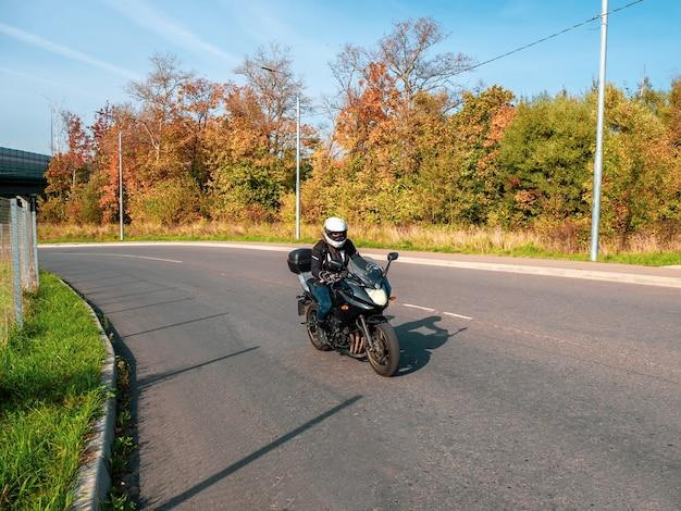 Motocyklista w ruchu. rowerzysta kobieta na czarnym motocyklu w ruchu na wiejskiej drodze jesień.