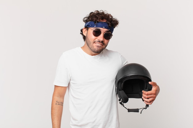 Motocyklista wyglądający na zdziwionego i zdezorientowanego, przygryzający wargę nerwowym gestem, nie znający odpowiedzi na problem