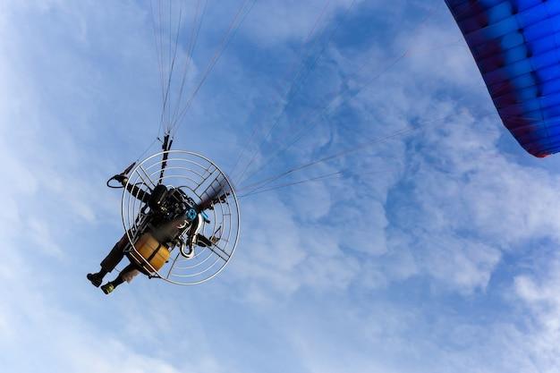 Motorowy paraglider latanie w niebieskim niebie z biel chmurą
