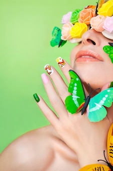 Motyle na paznokciach i ozdobne rozety na oczach kobiety
