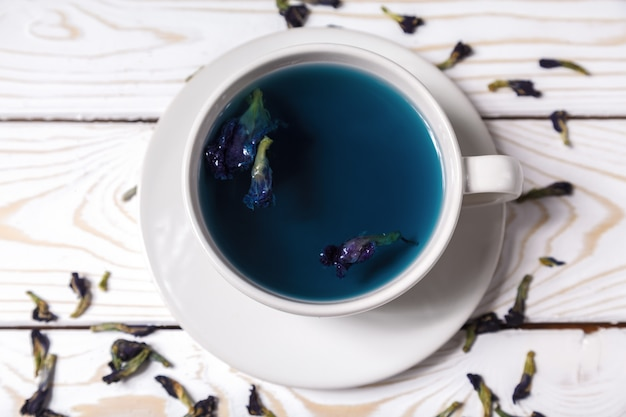 Motylka grochowa niebieska herbata kwiatowa w białej filiżance. zdrowy napój ziołowy detox. motyl groszek niebieska herbata anchan w widoku z góry cup