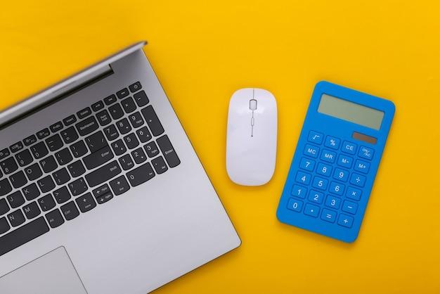 Motyw biznesowy. laptop z kalkulatorem na żółtym tle. widok z góry