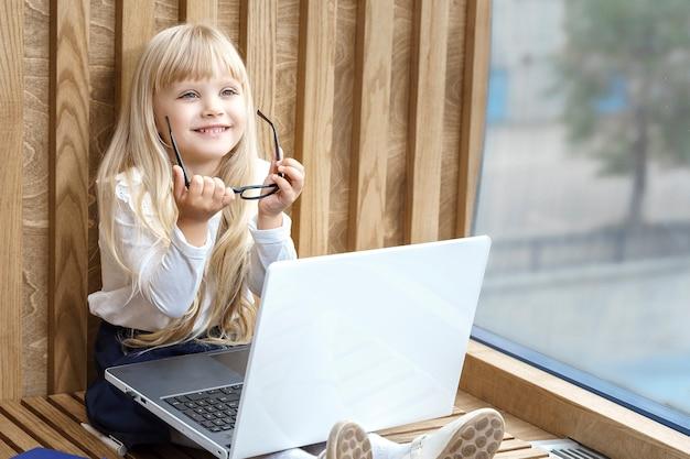 Motyw biznesowy. młoda piękna dziewczyna siedzi w miejscu pracy z laptopem w pobliżu okna