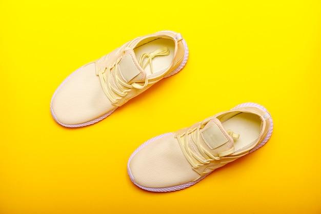 Motyw butów sportowych w żółtym kolorze. para żółci sneakers na żółtym tle. modny letni kolor.