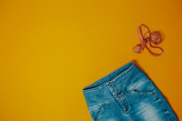Motyw diety i odchudzania. niebiescy dżinsy i pomarańczowa pomiarowa taśma z kopii przestrzenią.