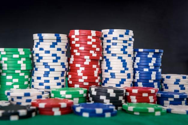 Motyw hazardu. kolorowe żetony do gry w stosach na zielonym stole z bliska