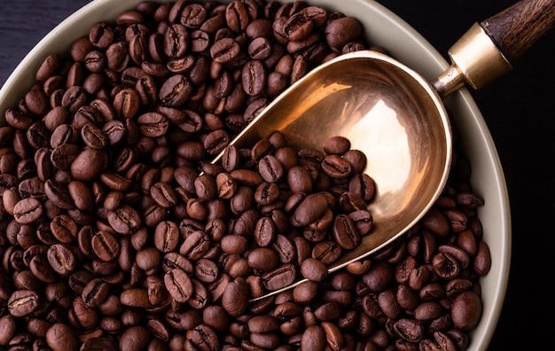 Motyw kawowy. talerz z ziaren kawy na czarnym drewnianym stole. vintage łyżka.
