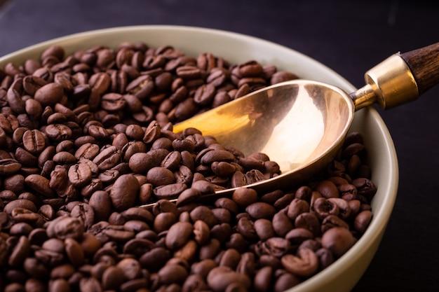 Motyw kawowy. talerz z ziaren kawy na czarnym drewnianym stole.