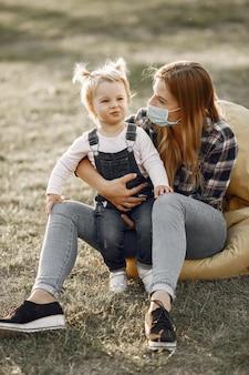 Motyw koronawirusa. rodzina w letnim parku. kobieta w koszuli z komórki.