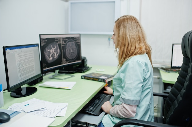 Motyw medyczny. lekarz w gabinecie rezonansu magnetycznego w centrum diagnostycznym w szpitalu, siedząc w pobliżu monitorów komputera.