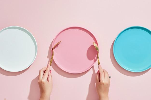 Motyw restauracja i jedzenie: ludzka ręka pokazuje gest na pustych trzech kolorowych talerzach na różowo