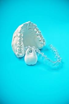 Motyw stomatologiczny ortodontyczny na niebieskiej powierzchni. przezroczyste niewidoczne nakładki dentystyczne lub szelki do leczenia ortodontycznego