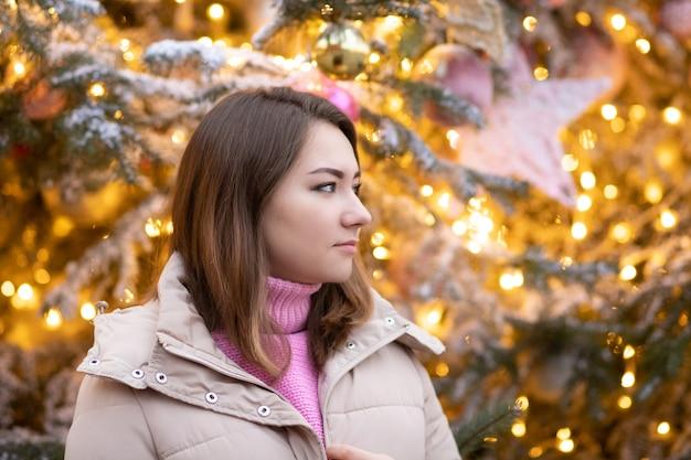 Motyw świąteczny. młoda piękna dziewczyna europejka na tle choinki, światełek i zabawek w radosnym nastroju, szczęśliwa, marzy o prezentach.