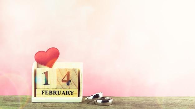 Motyw walentynki z drewnianym bloku kalendarza, czerwone serca i pierścienie. - 14 lutego.