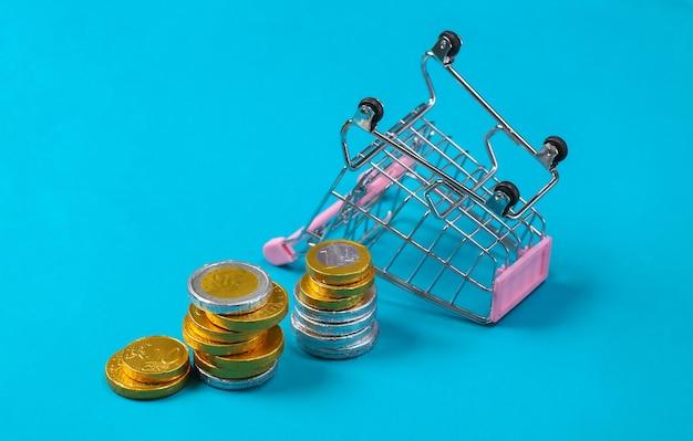 Motyw zakupów. mini supermarket wózek z monetami na bue.