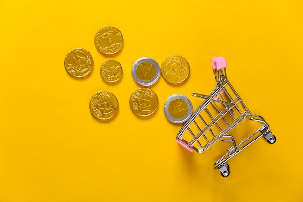 Motyw zakupów. mini supermarket wózek z monetami na żółto.