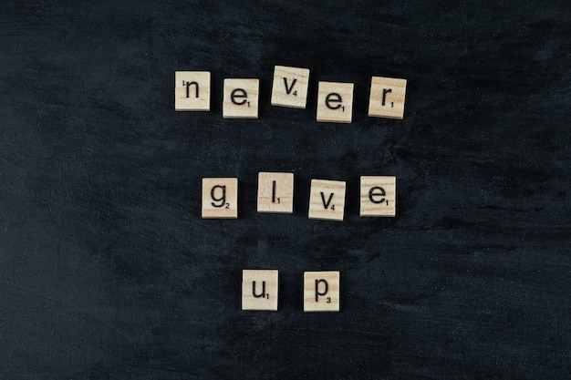 Motywacyjne i inspirujące cytaty z rzeźbionymi drewnianymi literami na tablicy.