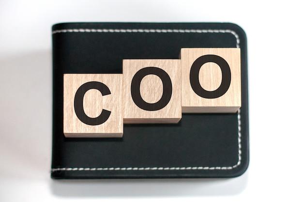 Motywacyjne słowa: dyrektor operacyjny w trójwymiarowych drewnianych literach alfabetu na powierzchni klawiatury