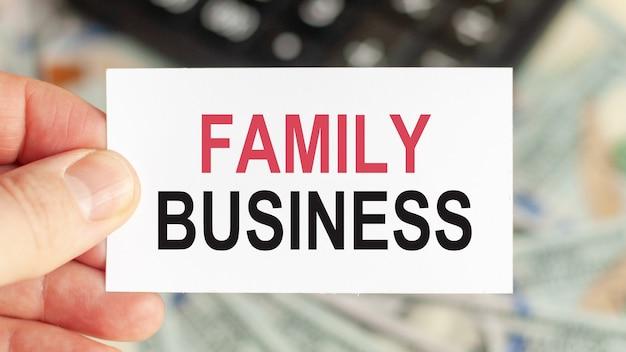Motywacyjne słowa: firma rodzinna. mężczyzna trzyma kartkę z tekstem: firma rodzinna.