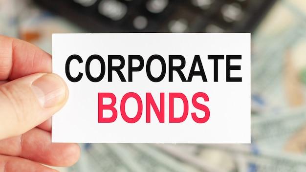 Motywacyjne słowa obligacje korporacyjne. mężczyzna trzyma kartkę papieru z tekstem obligacje korporacyjne.