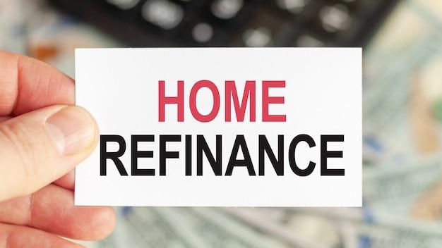 Motywacyjne słowa: refinansowanie domu. mężczyzna trzyma kartkę z tekstem: refinansowanie domu.