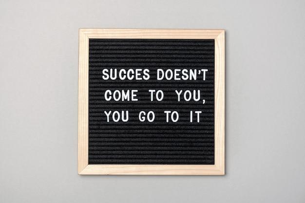 Motywacyjny cytat na czarnej tablicy na szaro