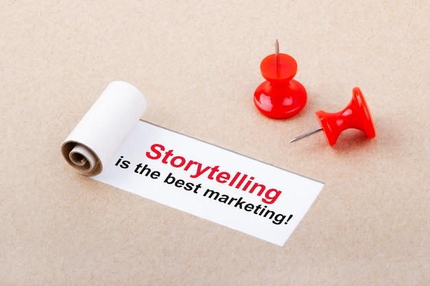 Motywacyjny cytat storytelling to najlepszy marketing, który pojawia się za podartym brązowym papierem
