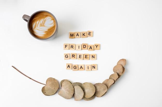 Motywujące hasło spraw, aby piątek znów stał się zielony. drewniane litery. widok z góry. kawa i eukaliptus