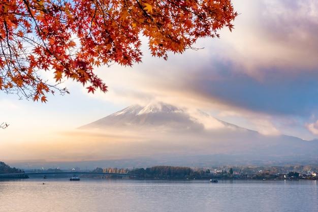Mount fuji przez mgłę z czerwoną pokrywą klonową w wschód słońca rano nad jeziorem kawaguchiko