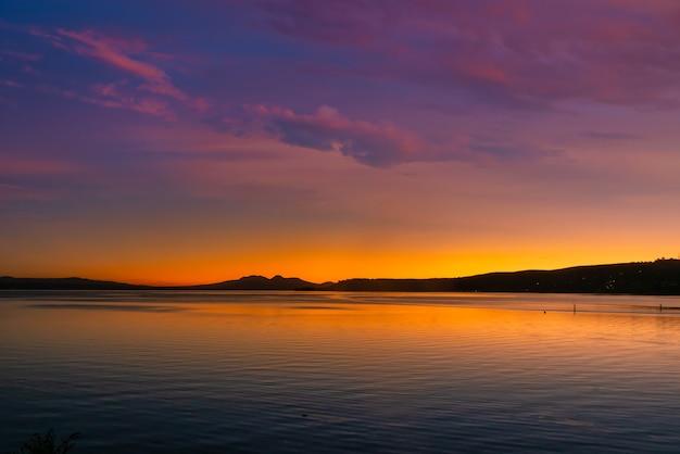 Mount ngauruhoe i góry wulkaniczne ruapehu w oddali, gdy zachód słońca zamienia się w noc widziany z jeziora taupo