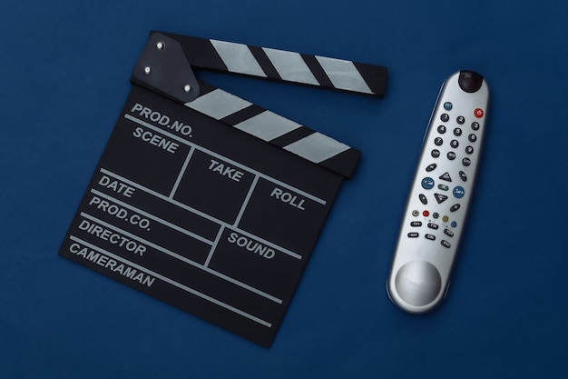 Movie clapper board i pilot do telewizora na klasycznym niebieskim tle. produkcja filmowa, produkcja filmowa, przemysł rozrywkowy. kolor 2020. widok z góry