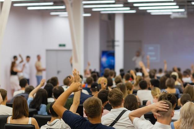 Mówca na podium. ludzie w sali konferencyjnej, widok z tyłu.