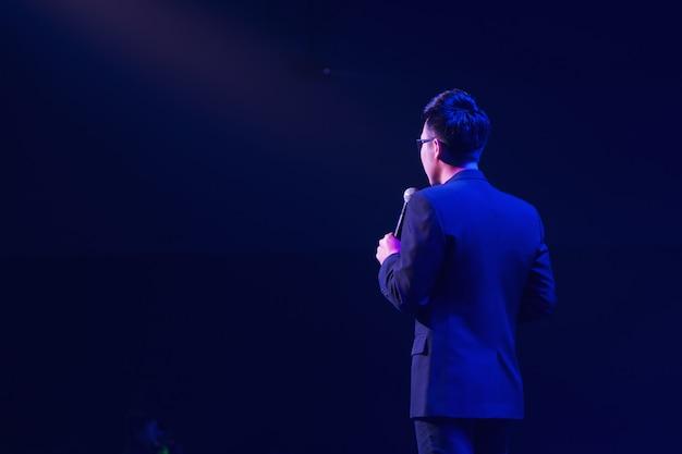 Mówca na scenie i wygłaszający rozmowę na spotkaniu biznesowym