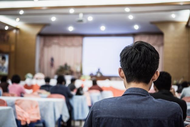 Mówca na scenie, publiczność z tyłu słucha wykładowcy w sali konferencyjnej lub seminarium