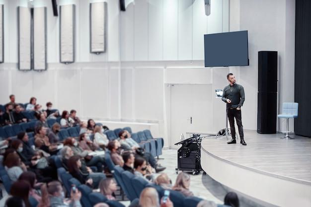 Mówca stojący na scenie w sali konferencyjnej