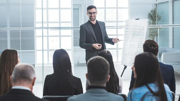 Mówca wskazuje na flipchart podczas prezentacji biznesowej