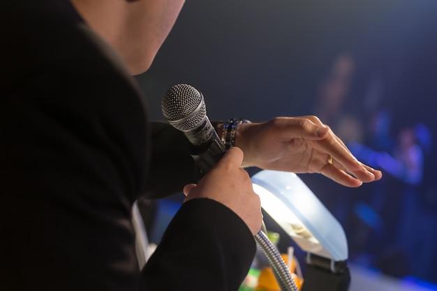 Mówca wygłasza przemówienie w korporacyjnej sali konferencyjnej lub sali seminaryjnej.