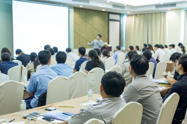Mówcy na scenie z widokiem z tyłu na widownię w sali konferencyjnej lub na spotkaniu seminaryjnym