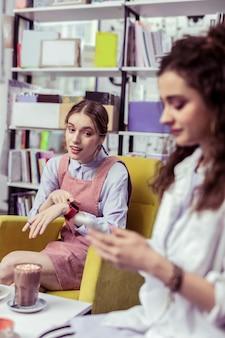 Mówi zbyt długo. rozczarowana długowłosa dziewczyna wskazuje na zegarek, akcentując uwagę swojej dziewczyny