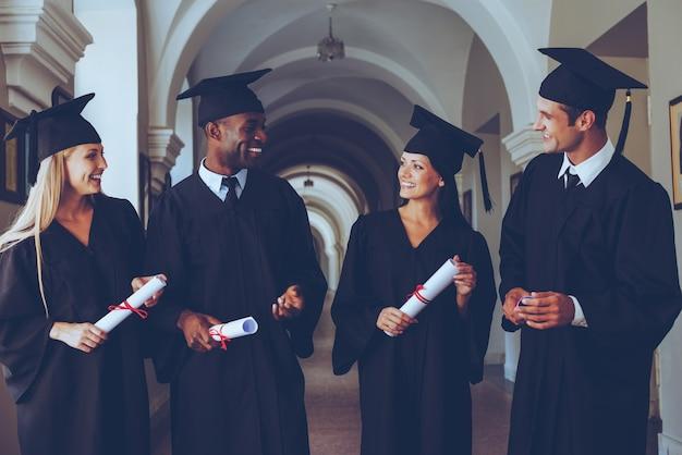 Mówiąc o świetlanej przyszłości. czterech absolwentów college'ów w sukniach dyplomowych spacerujących korytarzem uniwersyteckim i rozmawiających