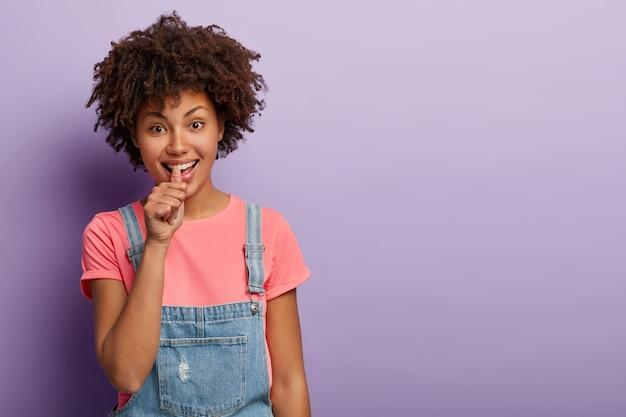 Mówię ci. młoda afro amerykanka pokazuje znak do postawienia zakładu, daje zakład