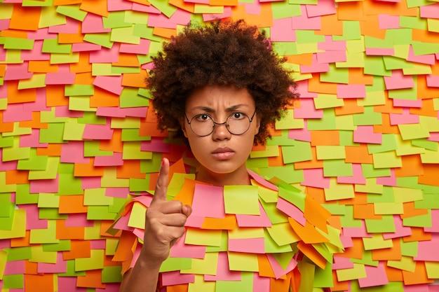 Mówiłem ci! zła niezadowolona ciemnoskóra kobieta ostrzega kogoś, podnosi palec z surowym wyrazem twarzy, pokazuje upominający gest, wystawia głowę, otoczona papierowymi kolorowymi samoprzylepnymi karteczkami