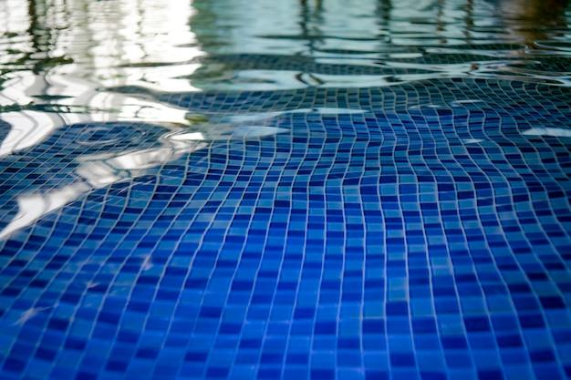 Mozaika lazurowego dna basenu aquaparku. widok na podłogę wyłożoną kafelkami przez czystą wodę krytego basenu. pulsuje i pulsuje na powierzchni wody w basenie krytym. odbicia światła i ciemności w basenie.
